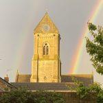 Rainbow in sky and church