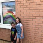 Children and drawing of rainbow in window